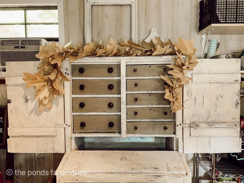 DIY Fall Leaf Garland displayed on a cabinet. Easy Fall Craft